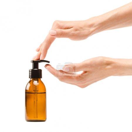 Photo pour Vue recadrée de femme pompant le savon de la bouteille de distributeur d'isolement sur le blanc - image libre de droit