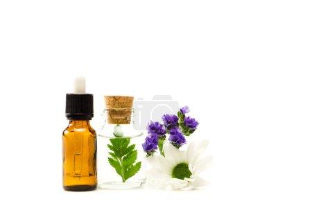 Photo pour Bouteilles avec liquide près de limonium et fleurs de chrysanthème isolés sur le blanc - image libre de droit