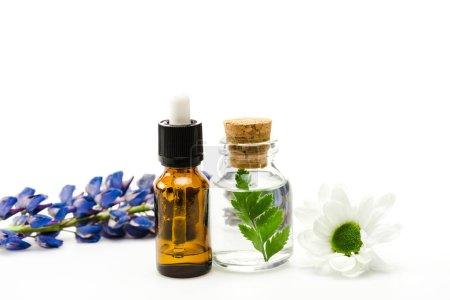 Photo pour Foyer sélectif des bouteilles avec le liquide près des fleurs isolées sur le blanc - image libre de droit