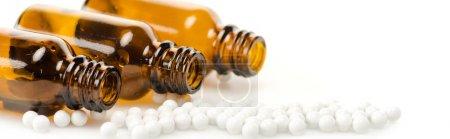 Photo pour Tir panoramique de pilules rondes près des bouteilles sur le blanc - image libre de droit