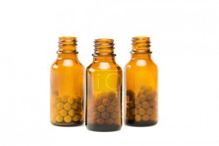 Photo pour Pilules rondes en petits flacons de verre orange isolés sur blanc - image libre de droit