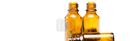 panoramic shot of small bottles with pills isolated on white
