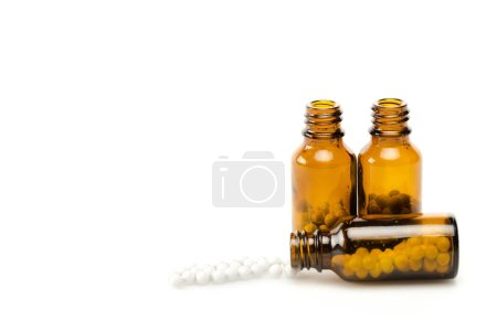 Photo for Small round pills near glass bottles isolated on white - Royalty Free Image