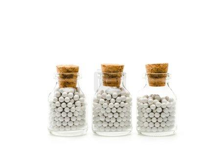Photo pour Bouteilles en verre avec pilules rondes et bouchons en bois isolés sur blanc - image libre de droit