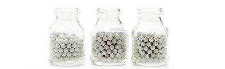Photo pour Plan panoramique de bouteilles en verre avec de petites pilules rondes isolées sur blanc - image libre de droit