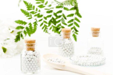 Photo pour Foyer sélectif de pilules dans des bouteilles en verre avec des bouchons en bois près de feuilles vertes sur blanc - image libre de droit