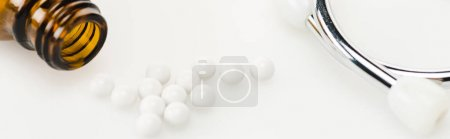 Photo for Panoramic shot of round small pills near stethoscope and glass bottle on white - Royalty Free Image