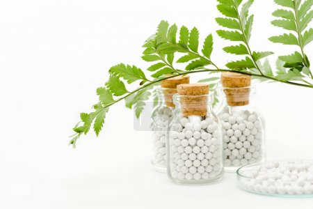 selective focus of medicine in glass bottles with wooden corks and green leaves on white