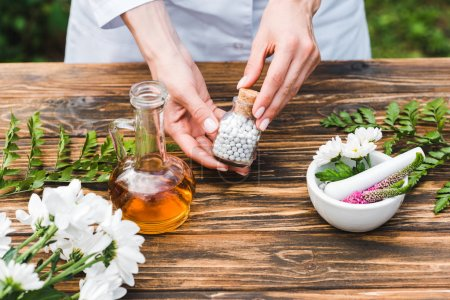 cropped view of woman holding bottle with pills near wooden table with plants