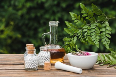 selective focus of pestle near mortar with flowers, glass bottles with pills and jug with oil on wooden table