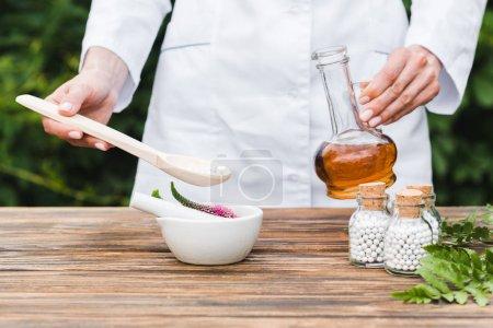 Foto de Vista recortada de la mujer sosteniendo cuchara con pastillas y botella de aceite cerca de mortero con flores de verónica y hojas verdes en la mesa de madera - Imagen libre de derechos