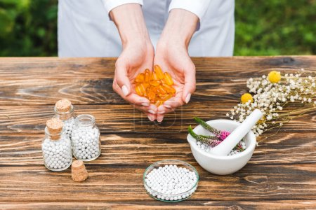 Photo for Cropped view of woman holding pills near bottles and mortar with veronica flowers on wooden table - Royalty Free Image