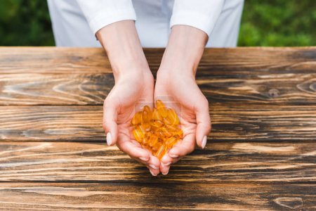 Photo for Cropped view of woman holding orange pills in hands near wooden table - Royalty Free Image
