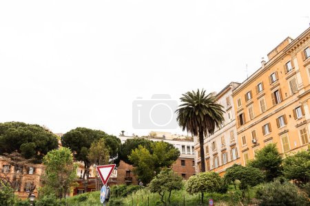 Photo pour Road sign, green trees and bushes near colorful buildings in rome, italy - image libre de droit