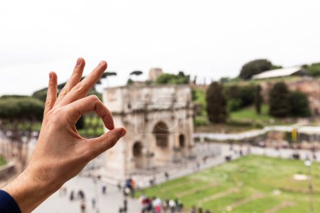 Photo for ROME, ITALY - JUNE 28, 2019: partial view of man showing okay sign in front of arch of constantine - Royalty Free Image