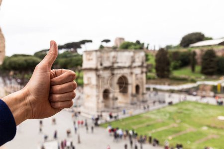 Photo for ROME, ITALY - JUNE 28, 2019: partial view of man showing thumb up in front of arch of constantine - Royalty Free Image