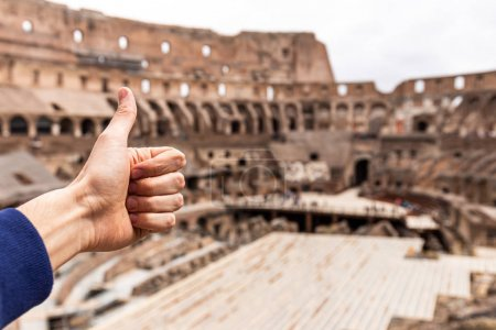 Photo for ROME, ITALY - JUNE 28, 2019: partial view of man showing thumb up in front of Colosseum - Royalty Free Image