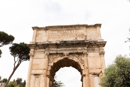 Photo for ROME, ITALY - JUNE 28, 2019: Arch of Titus and green trees under grey sky - Royalty Free Image