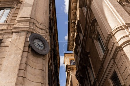 Photo for ROME, ITALY - JUNE 28, 2019: bottom view of buildings with street clock in rome, italy - Royalty Free Image