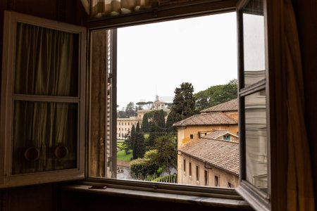 Photo for Building and green trees on street behind open window in rome, italy - Royalty Free Image