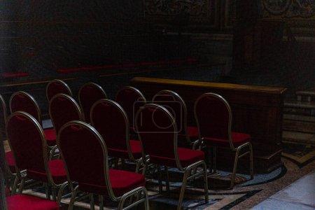 Photo pour Rome, Italie - 28 juin 2019: chaises rouges dans l'église sombre à Rome, Italie - image libre de droit