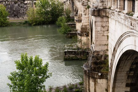 Photo for ROME, ITALY - JUNE 28, 2019: river Tiber under old bridge - Royalty Free Image