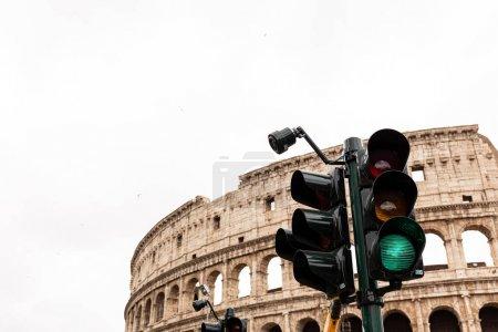 Photo pour ROME, ITALY - JUNE 28, 2019: colosseum and traffic light under grey sky - image libre de droit