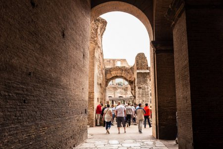 Photo for ROME, ITALY - JUNE 28, 2019: full length view of group of tourists walking near ancient buildings - Royalty Free Image