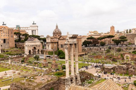 Photo for ROME, ITALY - JUNE 28, 2019: tourists walking around roman forum under grey sky - Royalty Free Image