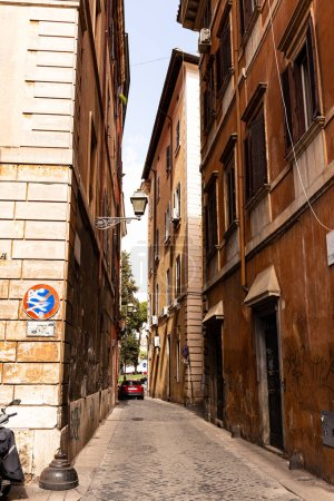 ROME, ITALY - JUNE 28, 2019: narrow street and red car in sunny day in rome, italy