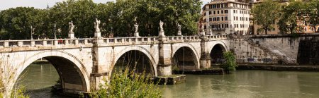 Photo pour ROME, ITALY - JUNE 28, 2019: panoramic shot of river Tiber and people walking on old bridge in sunny day - image libre de droit