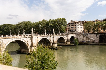 Photo for ROME, ITALY - JUNE 28, 2019: river Tiber and people on old bridge under cloudy sky in sunny day - Royalty Free Image