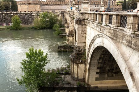 Photo for ROME, ITALY - JUNE 28, 2019: river Tiber and people on old bridge under cloudy sky - Royalty Free Image