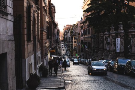 Photo for ROME, ITALY - JUNE 28, 2019: people and cars on street near old buildings - Royalty Free Image