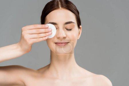 Photo pour Belle femme nue couvrant l'oeil avec le tampon de coton d'isolement sur le gris - image libre de droit