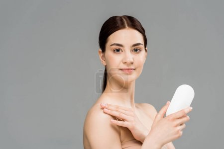 Photo for Happy young woman holding bottle with body lotion isolated on grey - Royalty Free Image