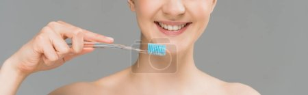 panoramic shot of happy naked woman holding toothbrush near teeth isolated on grey