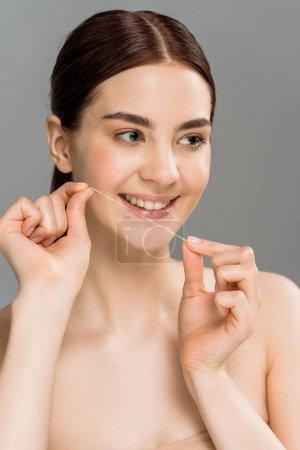Photo pour Femme gaire retenant la soie dentaire près des dents et souriant isolé sur le gris - image libre de droit