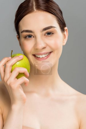 Photo for Happy woman smiling while holding green apple isolated on grey - Royalty Free Image