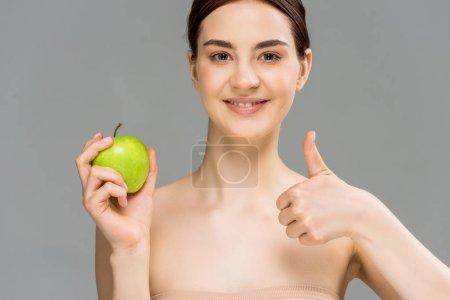 Photo pour Femme heureux souriant tout en retenant la pomme verte et affichant le pouce vers le haut d'isolement sur le gris - image libre de droit