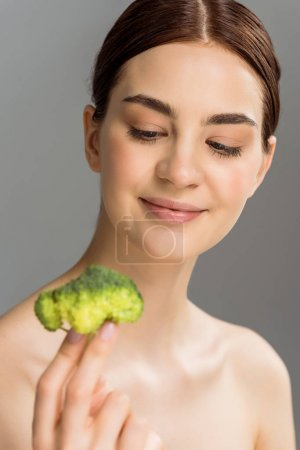 Photo for Selective focus of happy naked woman smiling while holding green broccoli isolated on grey - Royalty Free Image