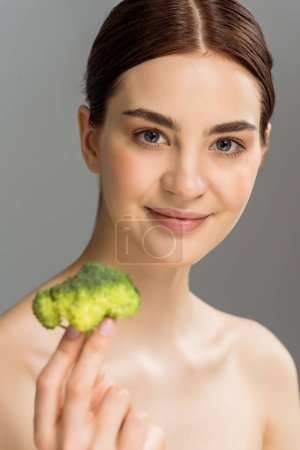 Photo for Selective focus of cheerful naked woman smiling while holding green broccoli isolated on grey - Royalty Free Image