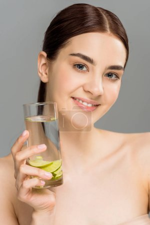 Photo for Cheerful girl holding glass of water with sliced lime isolated on grey - Royalty Free Image