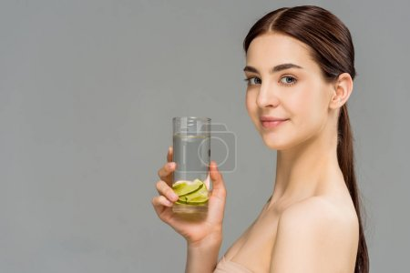 Photo for Cheerful young woman holding glass of water with sliced lime isolated on grey - Royalty Free Image