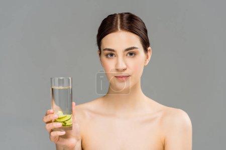 Photo pour Jeune femme attirante retenant le verre de l'eau avec la chaux tranchée s'est isolée sur le gris - image libre de droit