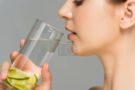 Photo pour Vue latérale de la jeune femme regardant un verre d'eau avec de la chaux tranchée isolée sur du gris - image libre de droit