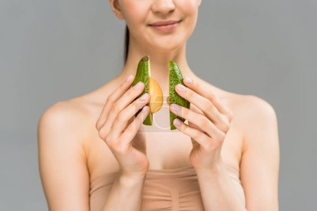 cropped view of happy young woman holding avocado halves isolated on grey