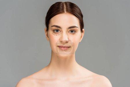 Foto de Mujer desnuda con marcas en la cara mirando la cámara aislada en gris - Imagen libre de derechos