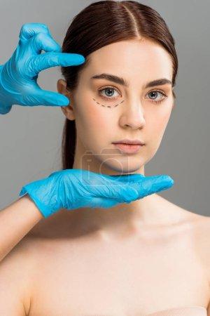 Foto de Vista recortada del cirujano plástico en guantes de látex cerca de una mujer atractiva con marcas en la cara aisladas en gris - Imagen libre de derechos