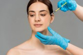cropped view of plastic surgeon making beauty injection to woman isolated on grey